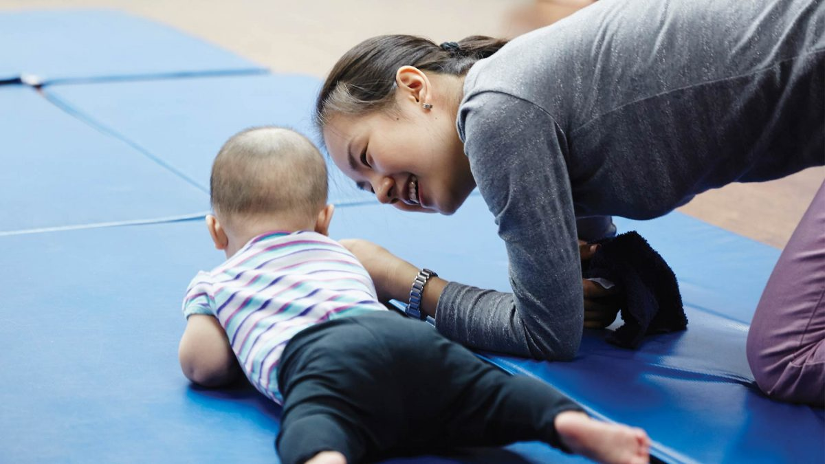 A mother and hey baby playing on a mat